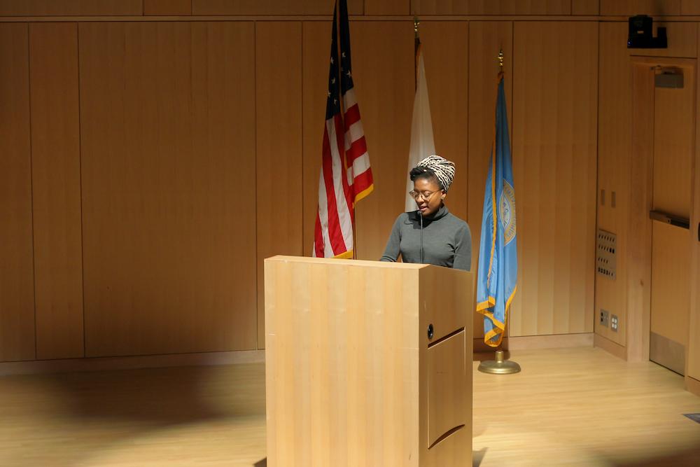 Simone John stands behind a podium.